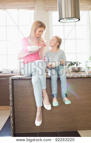 Mother and daughter looking at each other while having breakfast in kitchen