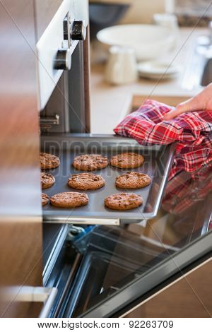Cropped image of woman's hand removing cookie tray from oven in kitchen