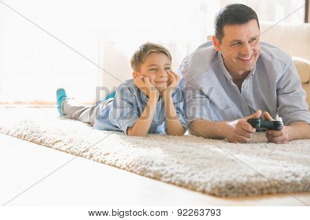 Happy father and son playing video game on floor at home