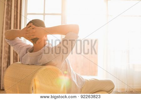 Rear view of man relaxing on chair at home