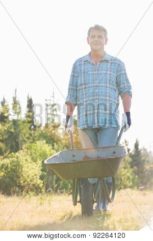 Portrait of male gardener pushing wheelbarrow at garden