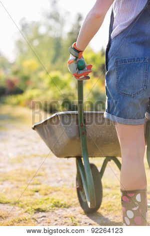 Midsection rear view of female gardener pushing wheelbarrow at plant nursery
