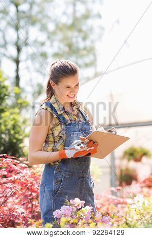 Happy female supervisor writing on clipboard outside greenhouse