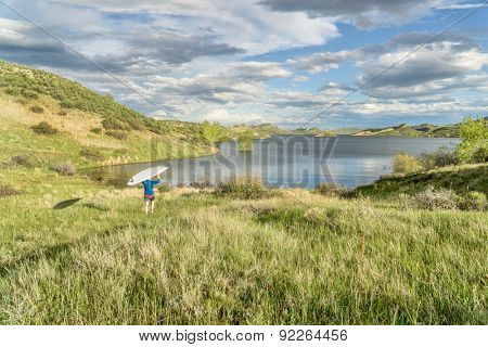male paddler is carrying hi SUP paddleboard to a lake - Horsetooth Reservoir near Fort Collins, Colorado, at springtime