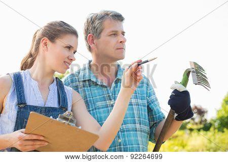 Female supervisor explaining something to gardener at plant nursery