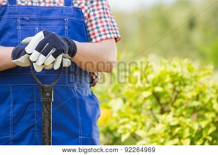 Midsection of gardener holding spade in plant nursery