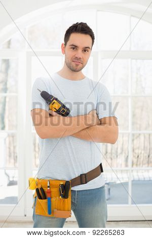 Portrait of confident man with hand drill in new house