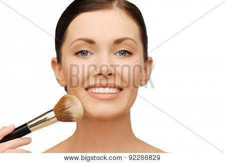 beauty and make-up concept - woman applying powder foundation with brush