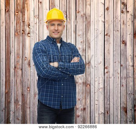 repair, construction, building, people and maintenance concept - smiling male builder or manual worker in helmet over blue background over wooden fence background