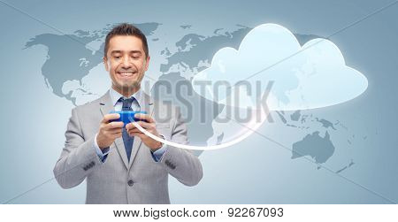 business, people, cloud computing and technology concept - happy businessman texting or reading message on smartphone over blue world map and cloud background