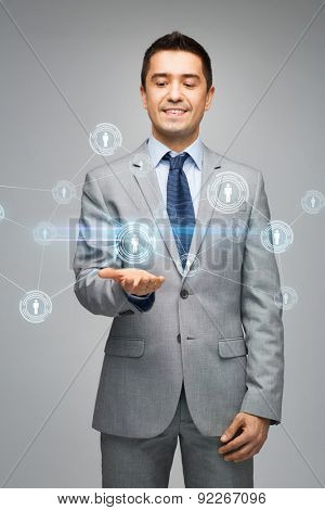 business, people, technology, connection and communication concept - happy businessman in suit showing network contacts over gray background