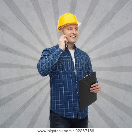 construction, building, people, technology and maintenance concept - smiling male builder or manual worker in helmet with clipboard calling on smarphone over gray burst rays background