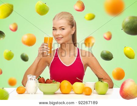 healthy eating, diet, detox and people concept - happy young woman having breakfast and drinking orange juice over green background with falling fruits