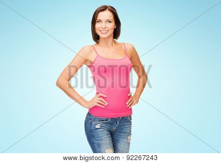 people, advertisement and clothing concept - smiling woman in blank pink tank top over blue background