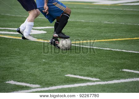 Legs of adult, male soccer player turning ball next to defender