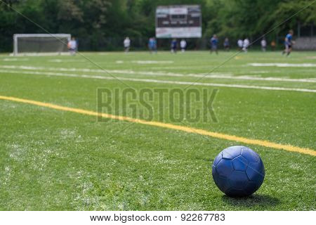 Soccer ball on field with teams, goal, scoreboard in background