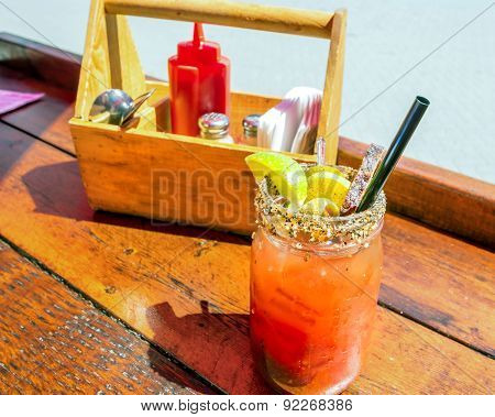 Caesar or bloody mary cocktail drink rimmed with spice and garnished.