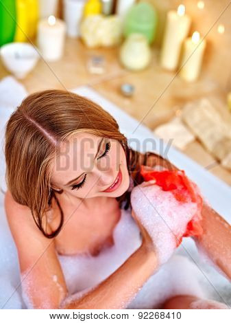 Woman holding red wisp of bast and taking bath.