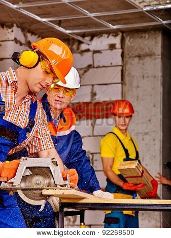 Happy group people  builder with circular saw working indoor.