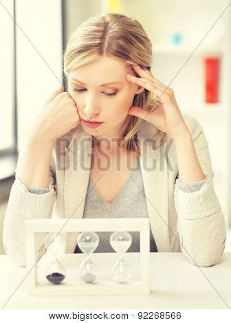 picture of pensive businesswoman with sand glass