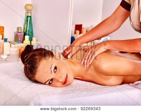 Woman getting back massage in beauty spa.