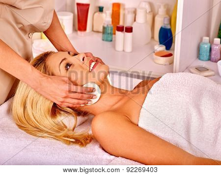 Young woman getting facial  classical massage in beauty spa.