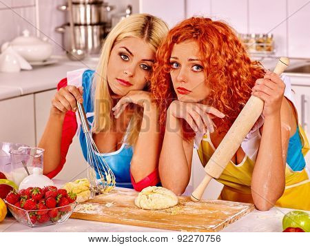 Young sad woman blond and red  baking cookies in oven.