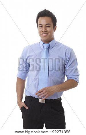 Portrait of smiling young Asian businessman standing hand in pocket, looking at camera.