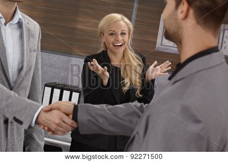 Businesswoman smiling happy, clapping hands over successful business agreement sealed with handshake.