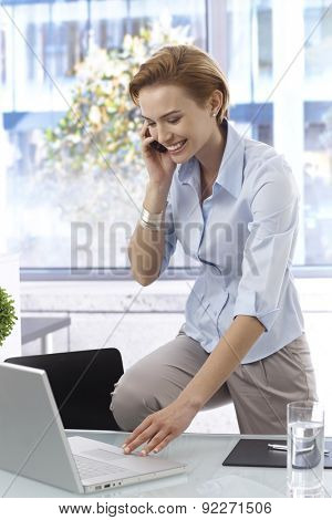 Happy young businesswoman talking on mobilephone, working with laptop computer, smiling.