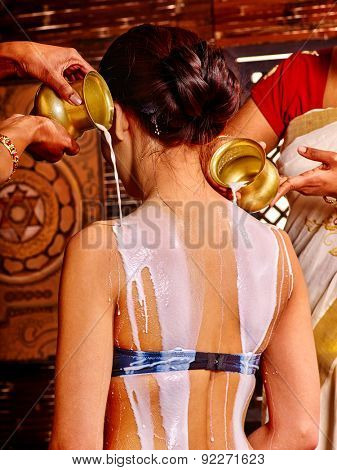 Woman having Ayurvedic spa treatment. Pouring milk.