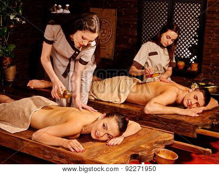Couple  having oil Ayurveda spa treatment. Two masseuses are making massage.