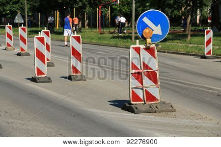 Road works marked with red and white striped road warning posts