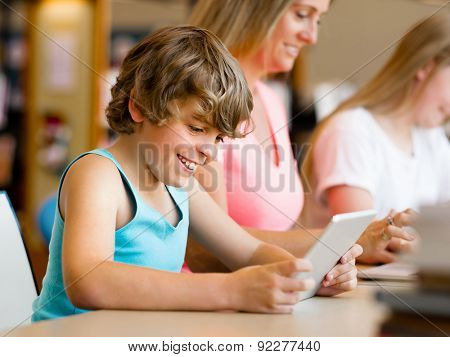 Boy with his famile on background in library with computer
