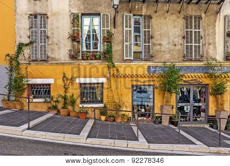 NICE, FRANCE - AUGUST 23, 2014: Pedestrian walkway along house with small gift shop in old Nice - fifth most populous and one of most visited cities in France with 4 million tourists every year.