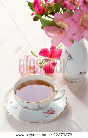 Retro still life with  cup of tea and flowers (Alstroemeria)
