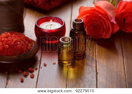 Essential oil, Mineral bath salts, candle and flowers on the brown  wooden table.
