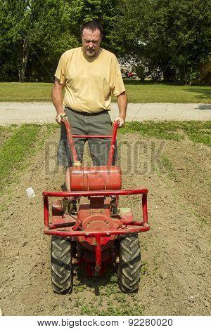 Front View Of Farmer Using A Garden Tiller