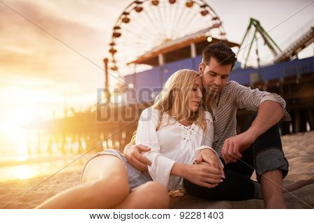 romantic moment with couple in the sand at  santa monica shot with selective focus and lens flare