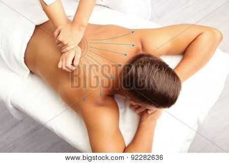 Back massage. Young man having back massage  (with arrows)