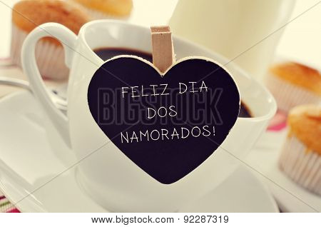 text Feliz Dia Dos Namorados, written in portuguese in a heart-shaped blackboard, for the holiday for lovers in Brazil, placed in a cup of coffee, with some muffins in the background in a set table