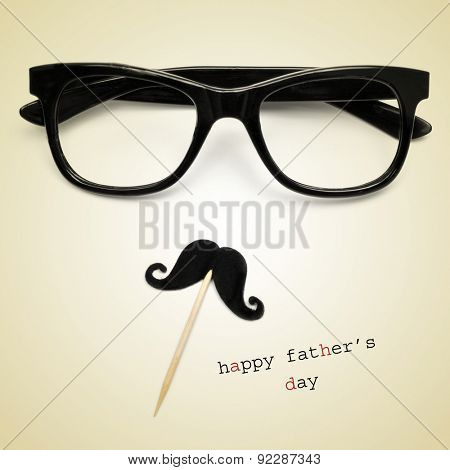 the sentence happy fathers day, and a pair black eyeglasses and a moustache forming a man face in a beige background