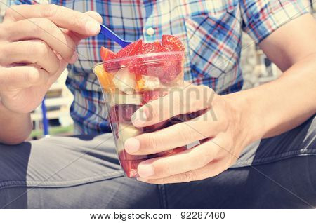 closeup of a young caucasian man wearing a plaid shirt eating a fruit salad in a clear plastic cup outdoors
