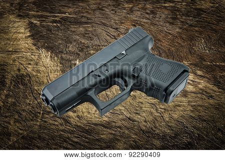 automatic 9mm. handgun pistol on bark tree background.