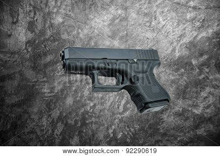 automatic 9mm. handgun pistol on cement wall background.
