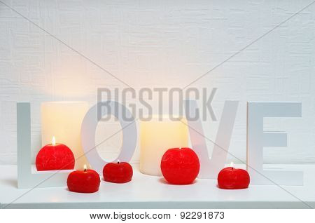 Romantic still life with word LOVE and candle lights on mantelpiece and white wall background