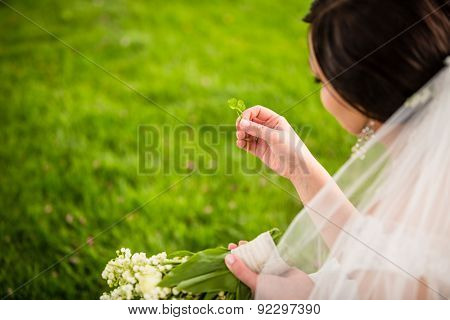 Bride on her wedding day with lucky fortune clover she has just found