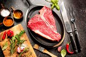 Постер, плакат: Raw fresh meat T bone steak and seasoning on dark background