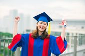 pic of graduation hat  - Portrait of a cheerful graduate in gown and graduation hat - JPG