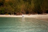 pic of barefoot  - bride and groom barefoot splash at edge of transparent water against tropical trees - JPG